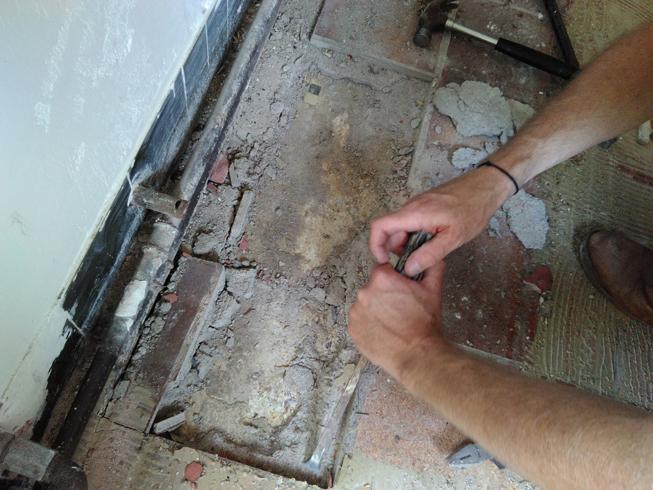 Onder de oude tegelvloer wordt de granito zichtbaar.
