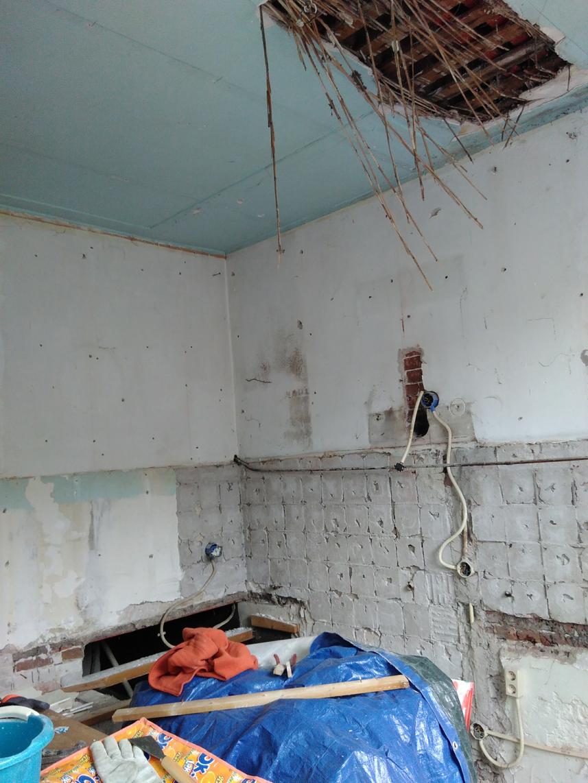 Keuken zonder tegels en met oud plafond deels eruit.