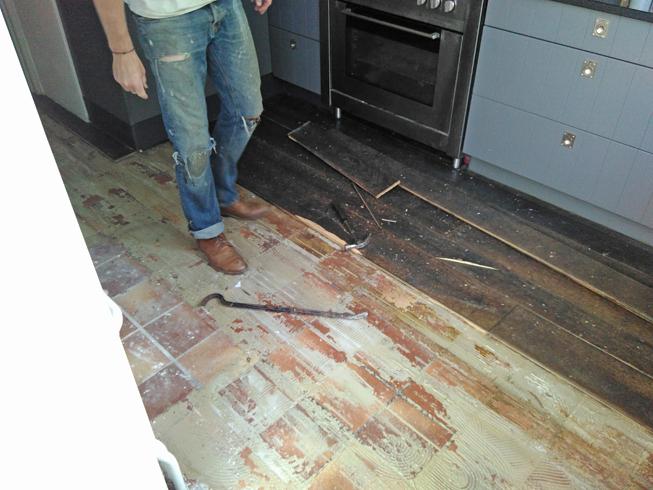 Frank verwijdert de houten vloer met daaronder de tegelvloer.